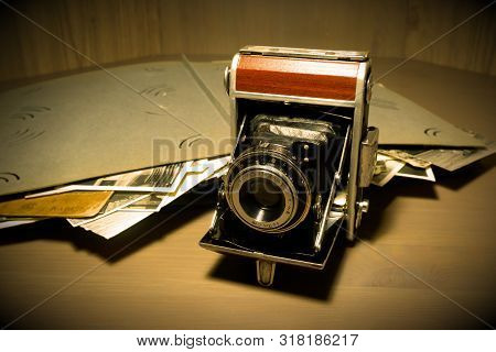 Retro Old Vintage Outdated Manual Film Camera Circa 1940s And Vintage Photo Album On Wooden Table. V