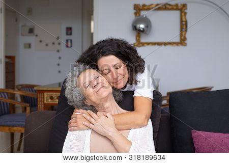 Mother And Daughter With Closed Eyes Hugging. Happy Senior Mother And Middle Aged Daughter Hugging T