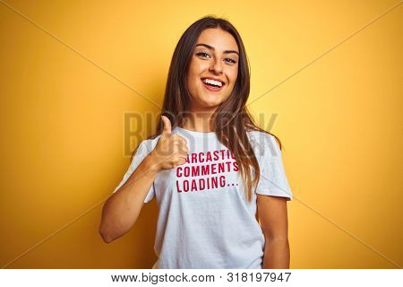 Beautiful woman wearing fanny t-shirt with irony comments over isolated yellow background doing happy thumbs up gesture with hand. Approving expression looking at the camera with showing success.