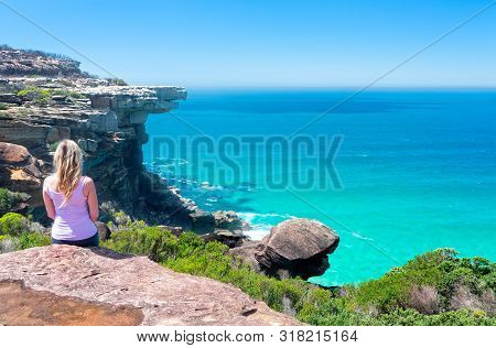 A Female Sitting On Cliffs By The Ocean With Views To Eagle Rock And Below Lovely Clarity In The Wat