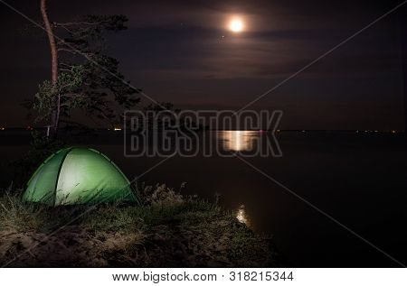 Camping For A Starry Night. The Tent Glows Under The Night Sky Full Of Stars