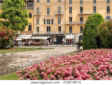 Cavour Square In Front Of The Lake Como With People Enjoying The Bars And Restaurants Outdoors In Su