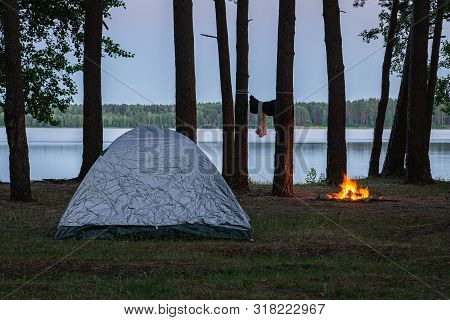 View of the campsite by the lake at twilight. Tent and burning fire place by the water surrounded by trees in the forest. Spending the night in wilderness poster