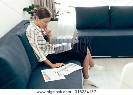 Profile Side View Of Young Adult Woman Sitting On Couch With Laptop Computer And Working With Docume