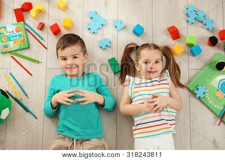 Little Children With Toys And Books Lying On Floor Indoors, Top View. Playtime