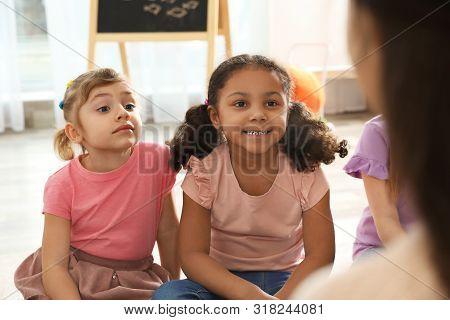 Cute Little Children Listening To Teacher Indoors. Kindergarten Playtime Activities