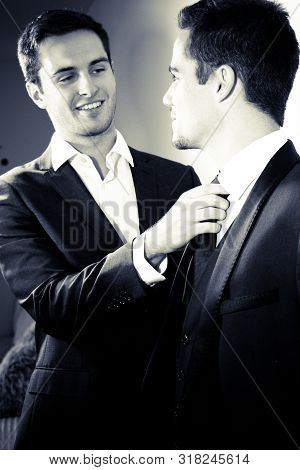 Smiling Male Gay Couple, One Looking At His Partner As He Fixes His Tie For Him.