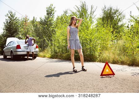 Young multiethnic couple broke down the car while traveling on the way to rest. They are trying to fix the broken by their own or should hitchhike, getting nervous. Relationship, troubles on the road, vacation. poster