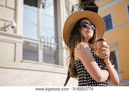 Pretty Girl In A Black Dress, Hat With Wide Flaps And Sun Glasses Holds Disposable Paper Cup Of Hot