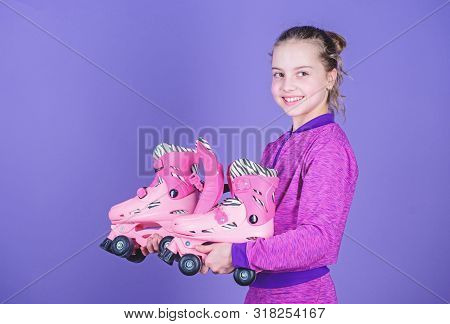 Learning To Skate Is Fun. Cute Little Skater. Small Girl Holding Pink Roller Skates. Little Child Wi