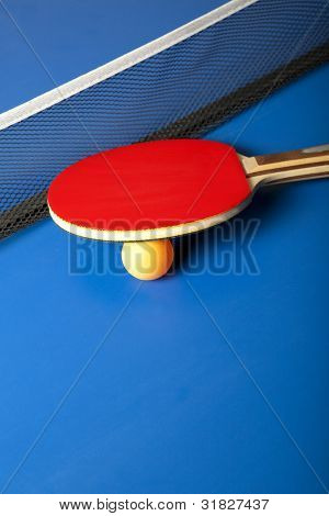 Table tennis or ping pong rackets and balls on a blue table