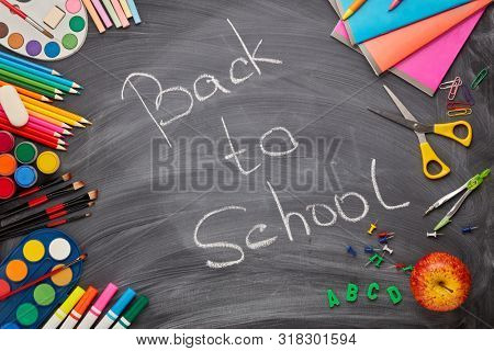 Stationery accessories on background of school blackboard with inscription: Back to school. Top view. School accessories for children's education and development.  Office supplies.