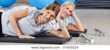 Two smiling women relaxing on gym mats in fitness center
