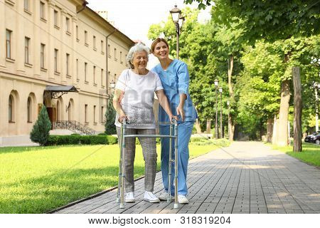 Happy Nurse Assisting Elderly Woman With Walking Frame At Park