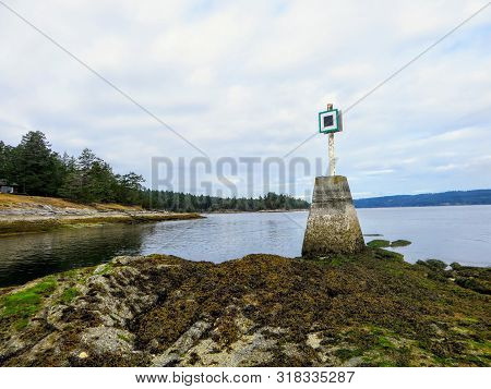 View Of A Port Hand Day Beacon At Low Tide At The End Of A Reef On An Island.  The Port Hand Day Bea