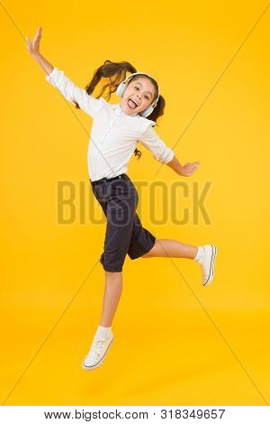Dancing Class. Small Dancer Moving To Music On Yellow Background. Little Child Enjoy Dancing To Mode
