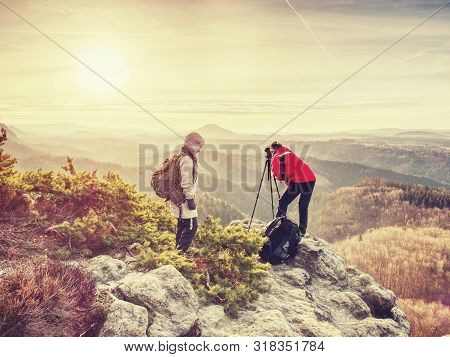 Tourists Couple Stay On Summit And Takes Memory Picture With Camera On Tripod.  Hiker And Photo Enth