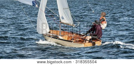 Children Sailing Small Traditional Wooden Sailboat Closeup On An Inland Waterway For Fun And In Comp