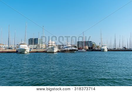 Group Of Yachts And Boats In The Marina Port Against The Backdrop Of A City Landscape