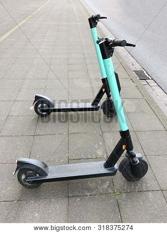 Two Electric Kick Scooters Or E-scooter Parked On Sidewalk - E-mobility Or Micro-mobility Trend