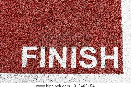 Bold Text Finish Is Painted At The Finish Line On A Red Track In White.