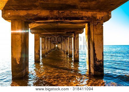 Diminishing Perspective Of Wooden Pillars Underneath Long Old Pier Standing In Ocean Water At Sunset