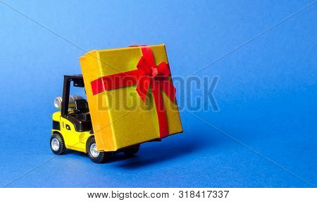 Yellow Forklift Truck Carries A Golden Yellow Gift Box With A Bow. Purchase And Delivery Of A Presen