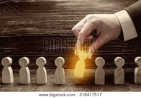 A Businessman Pulls A Glowing Golden Man Figure Out Of A Gray Crowd. The Concept Of Search Workers F