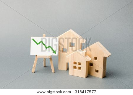 Wooden Houses And An Easel Arrow Down. The Fall Of The Real Estate Market. Concept Of Value Or Cost