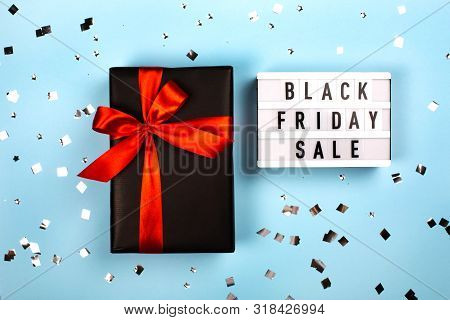 Lightboard With Letters And Black Gift Box With Red Ribbon. Black Friday Sale Concept.