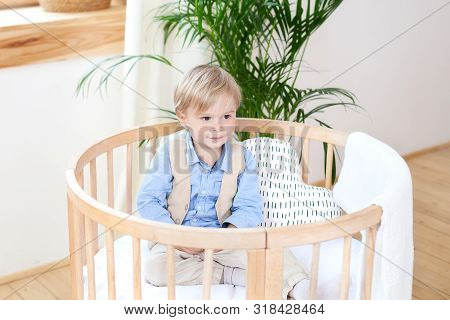 Portrait Of A Little Happy Boy Playing In A Baby Crib. The Boy Sits Alone In The Crib In The Nursery