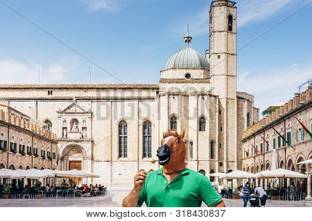 Horse Man Standing In The Middle Of The Historic Square Of Ascoli Piceno In Italy, Eating A Fried Ol