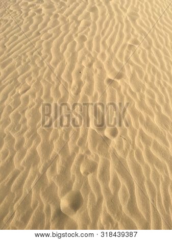 Close up of flat sand dune with wavy wind pattern in a stark desert.