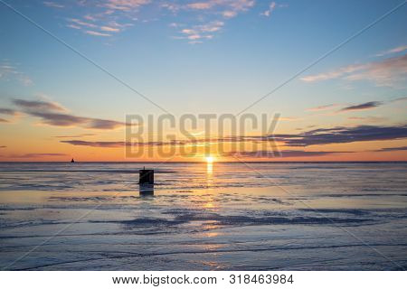 The sun setting over a frozen harbor and an ice fishing shack in rural Prince Edward Island, Canada. Lighthouse on the horizon.