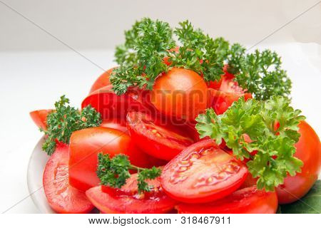 Slices Of Red Ripe Tomato And Fresh Herbs On A Plate In The Kitchen. Natural Authentic Still Lifes,