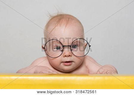 Funny Baby In Big Round Glasses At The Table. White Background. Smart Concept