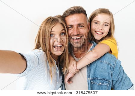 Image of adorable caucasian family woman and man with little girl smiling and taking selfie photo together isolated over white background