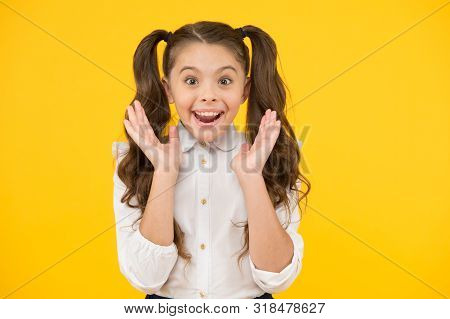 Back To School And Looking Delighted. Surprised Little Girl Smiling On Yellow Background. Small Chil