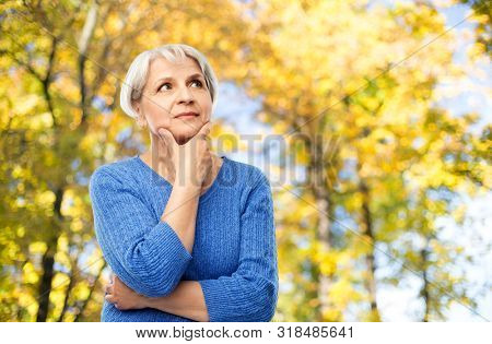 old people and decision making concept - portrait of senior woman in blue sweater thinking over autumn park background