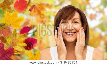 beauty, skin care and old people concept - portrait of smiling senior woman touching her face over autumn leaves and nature background