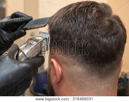 Hairstylist working with clipper and comb, close up view. Mans head and masters hands in black rubber gloves. Stylist at work in studio. Selective soft focus. Blurred background poster