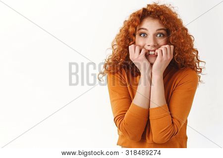 Excited cheerful attractive redhead woman curly haircut huge fan of singer attend breathtaking concert, feel overhwhelmed happy and thrilled, biting fingers eager receive autograph, white background poster