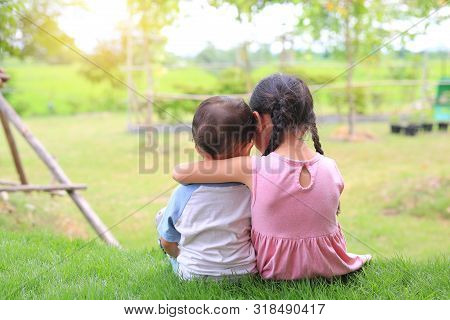 Older Sister Hugs Little Brother By The Neck, Shoulders Sitting On Green Grass Field. Two Adorable A