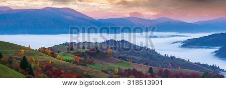 Wonderful Autumn Countryside In Mountains At Dawn. Valley Full Of Floating Cold Fog. Glowing Sky Abo