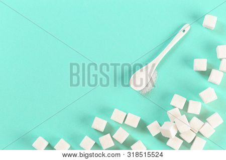.background Of Sugar Cubes And Sugar In Spoon. White Sugar On Turquoise Background. Sugar With Copy