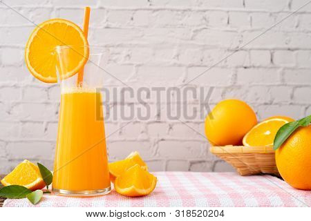 Kitchen Table With Jug Of Orange Juice And Orange Fruit In Basket On White Brick Wall Texture Backgr