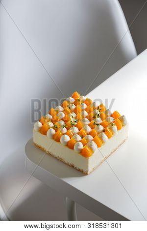 A Square Cream Cake Separated By Mango And Cream