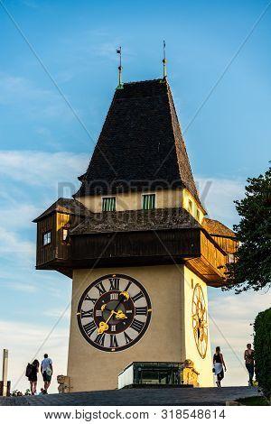 Graz, Austria - 17.08.2019 : View At Famous Clock Tower Uhrturm At Schlossberg Hill. Tourists Walkin