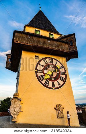 Graz, Austria - 17.08.2019 : View At Famous Clock Tower Uhrturm At Schlossberg Hill. Girl With Phone