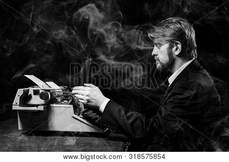 Writer, A Man In A Black Jacket Typing On Typewriter. Everything Is In The Smoke. Tobacco Harm Conce